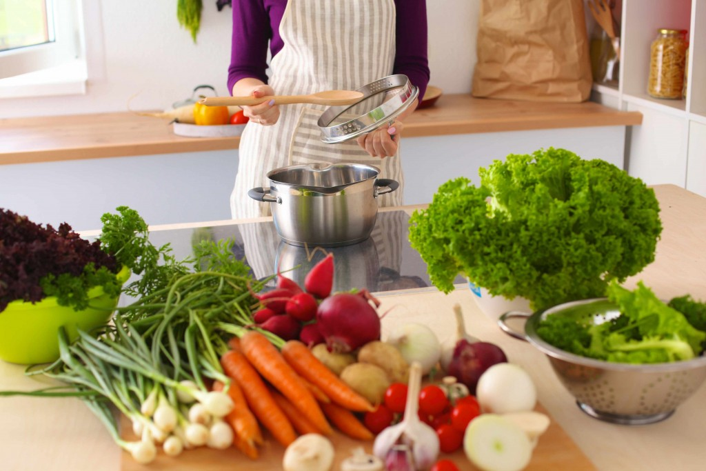 a chef in the kitchen with pots, pans and healthy vegetables