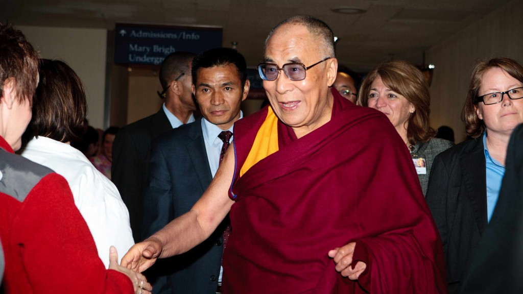 the Dalai Lama in a red robe and smiling