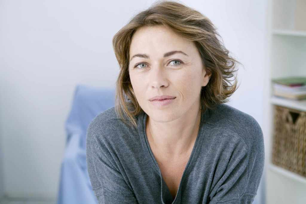 middle aged woman looking relaxed, thoughtful, calm, meditative
