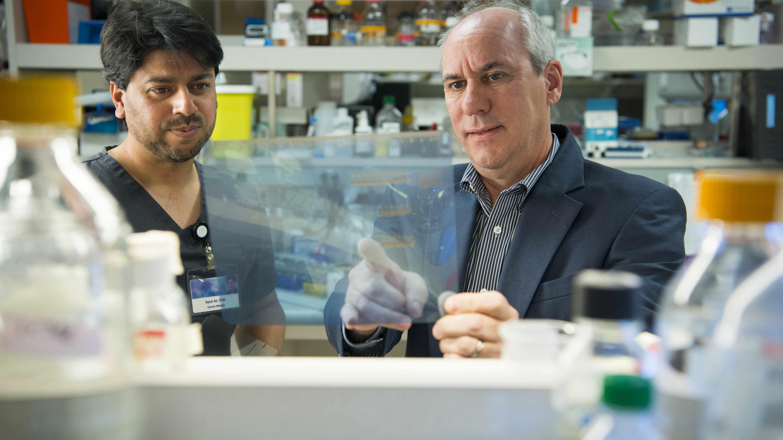 Dr. Alan Fields y un asistente del laboratorio