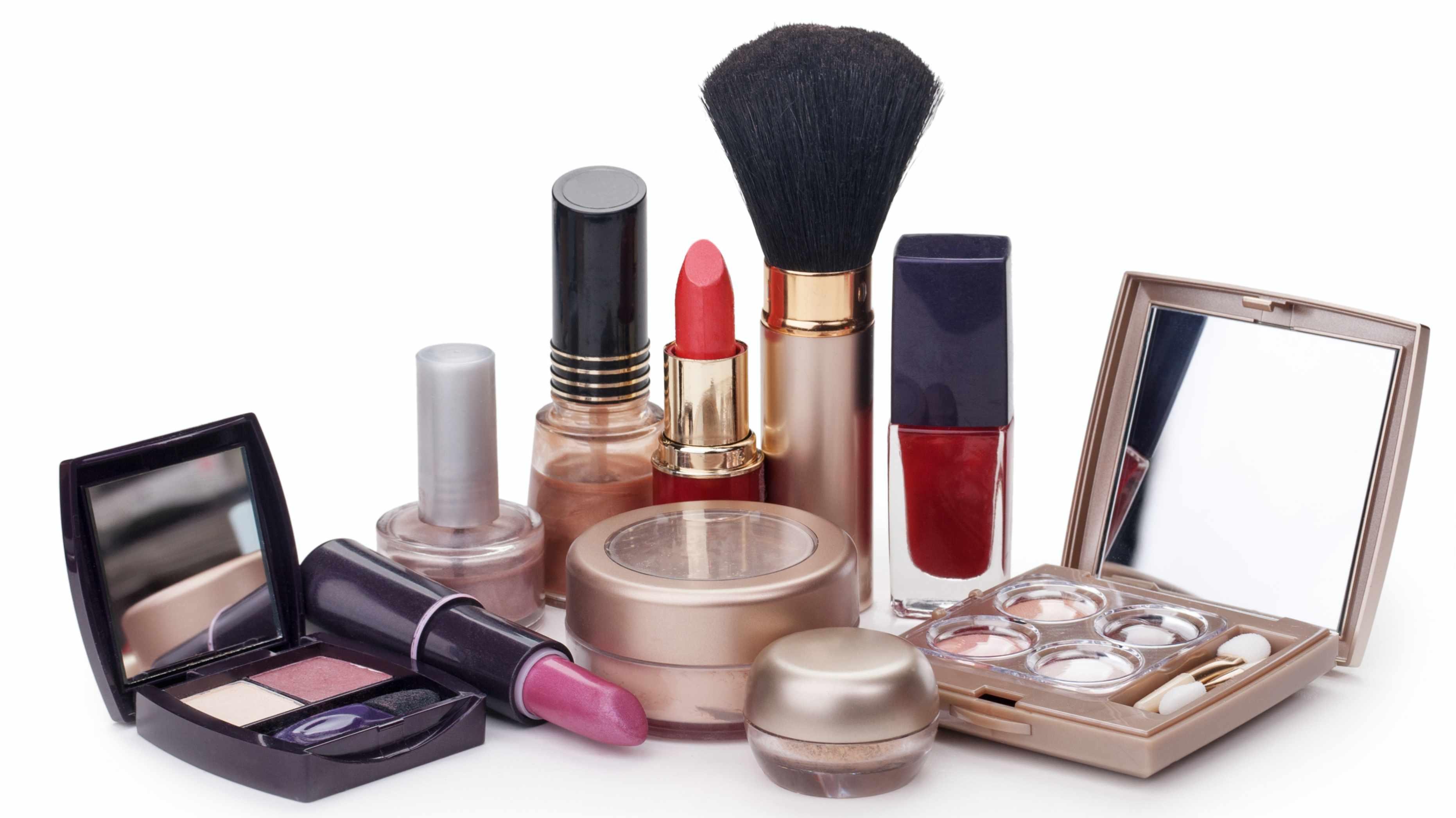 Productos de maquillaje distribuidos sobre una mesa, incluso con lápiz labial y sombra de ojos