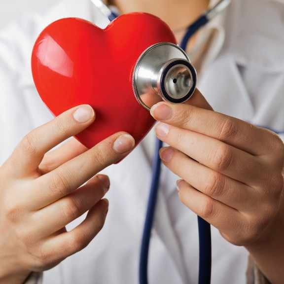 a health care provider in a white lab coat and stethoscope holding a red plastic heart