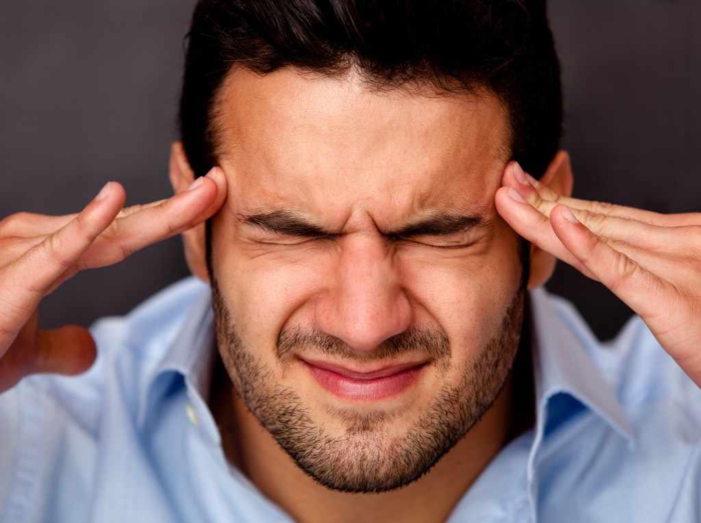 Hombre con los ojos cerrados, haciendo muecas y sosteniéndose las sienes