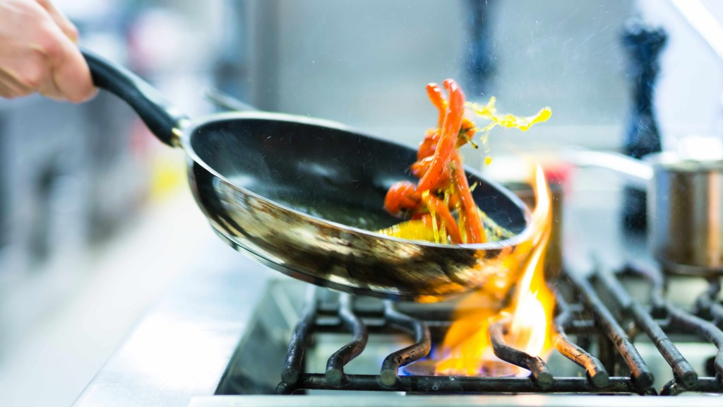 a person cooking at a stove with a frying pan and hot gas flames