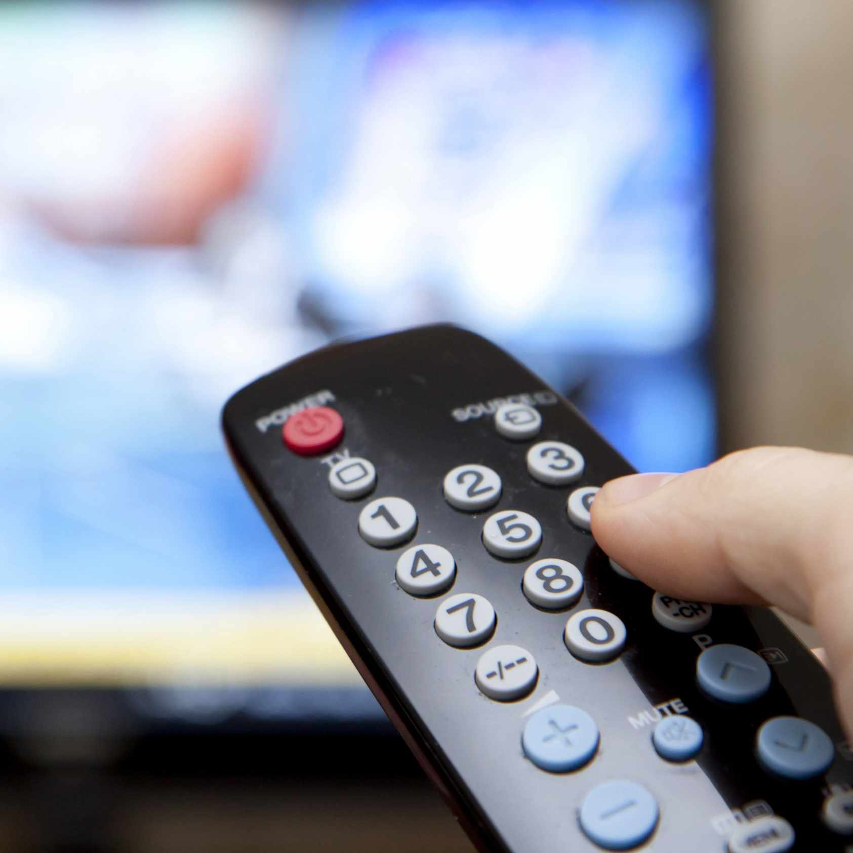 a person holding a television remote control with the TV blurred out in the background