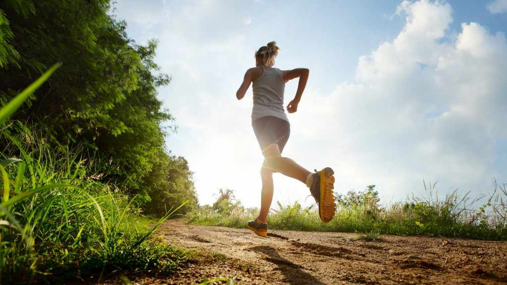 a woman running outside, up a trail, on a sunny day