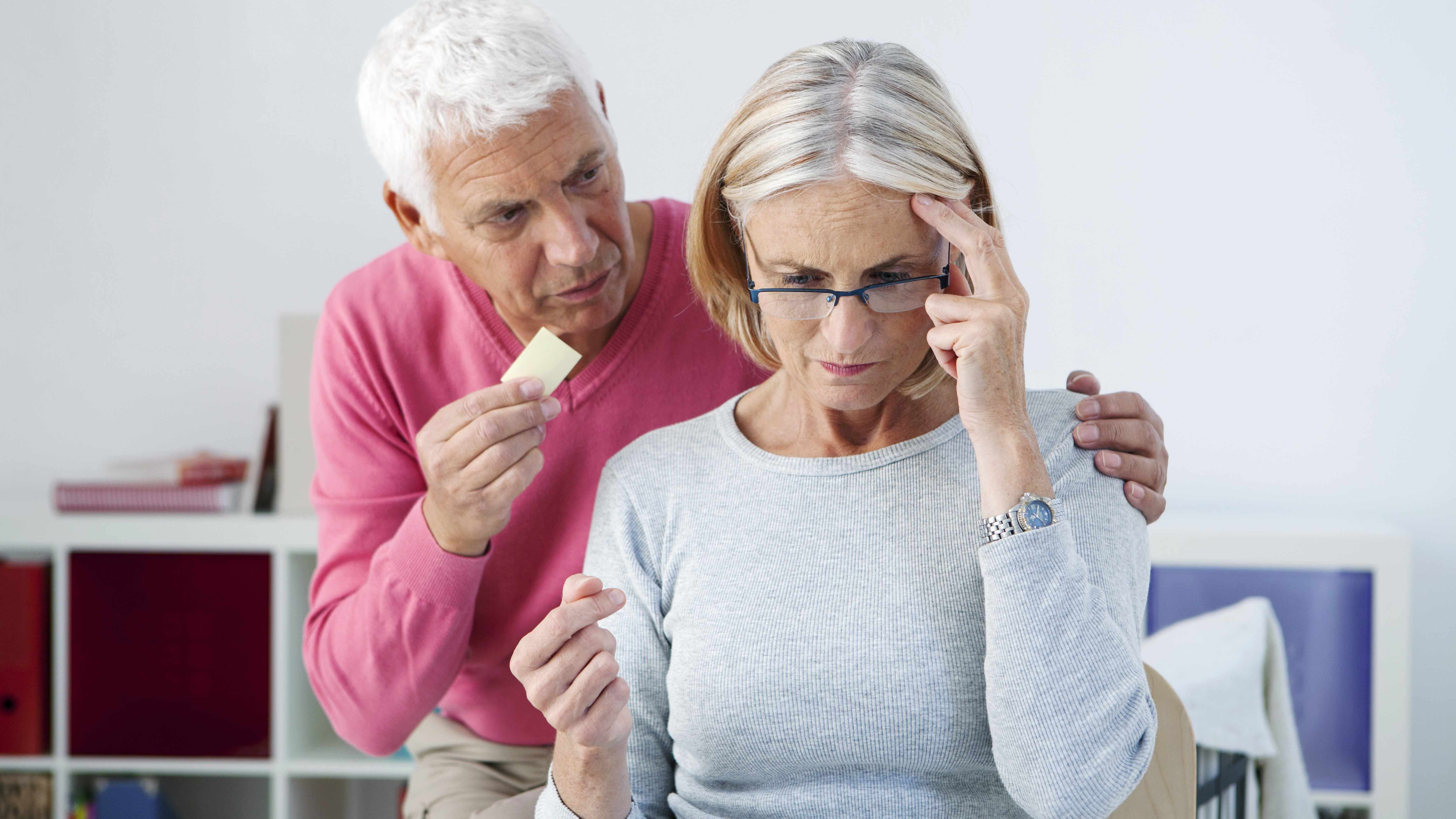 an older man showing a piece of paper to an older woman who is touching her head and trying to remember something