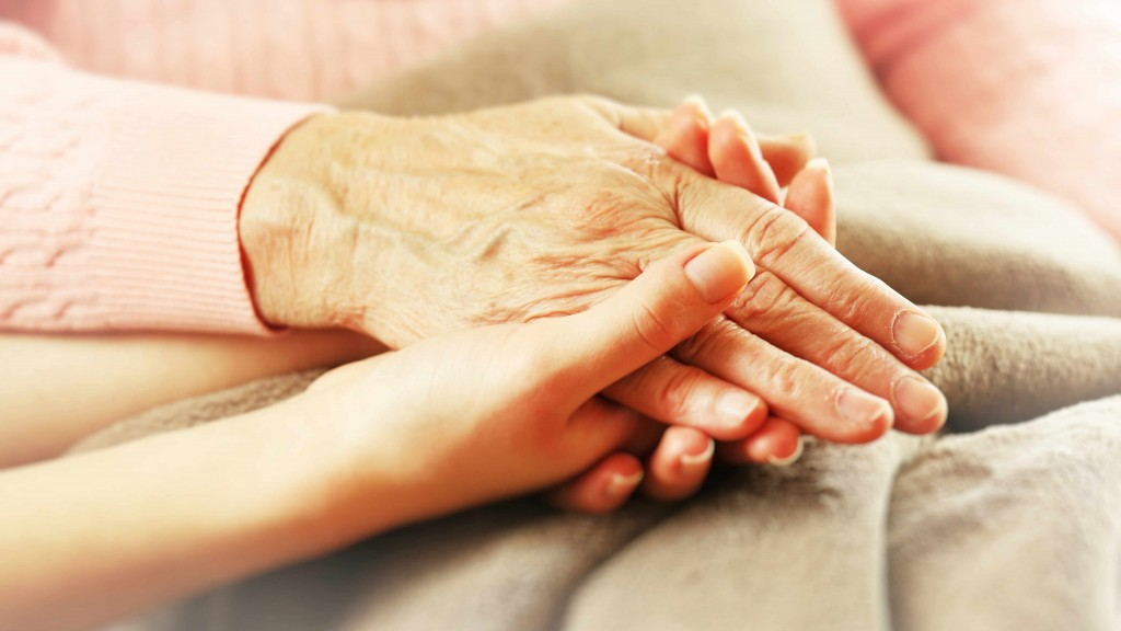 an older person's hand holding a child's hand