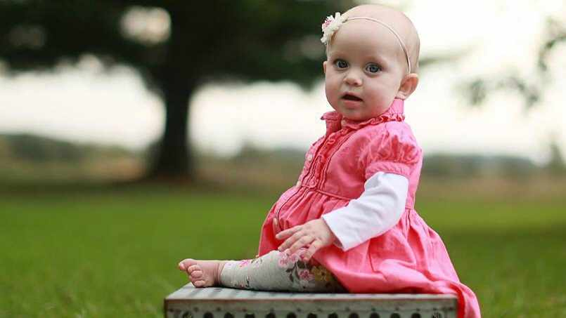 baby Mallory sitting outside on a stone bench 16x9