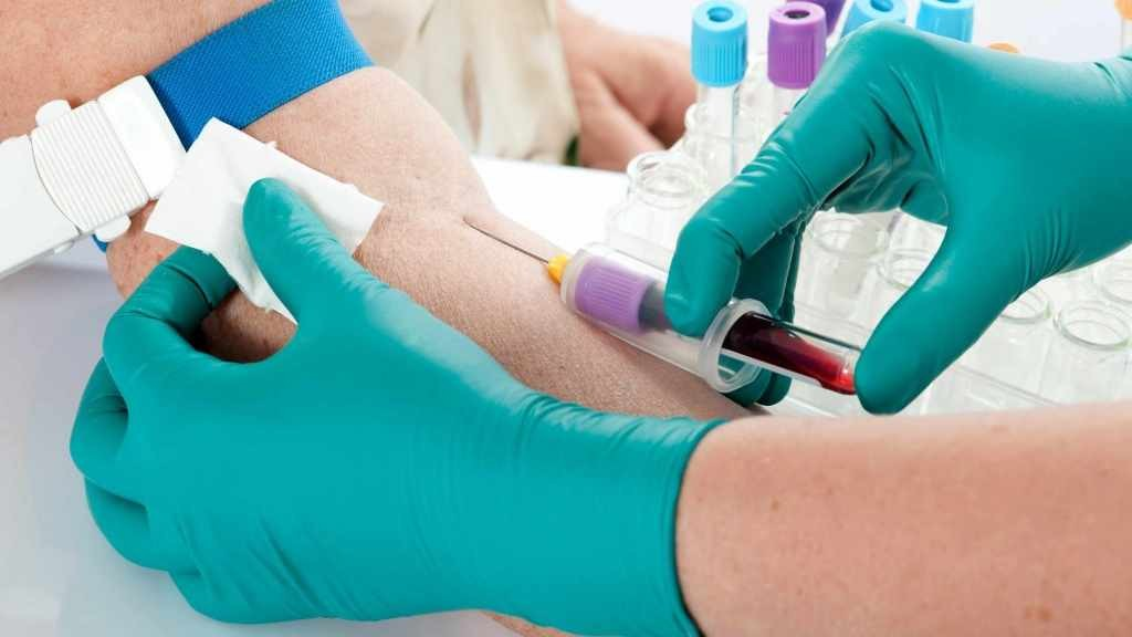 gloved hands of a health care provider using a needle to draw blood from the arm of a patient