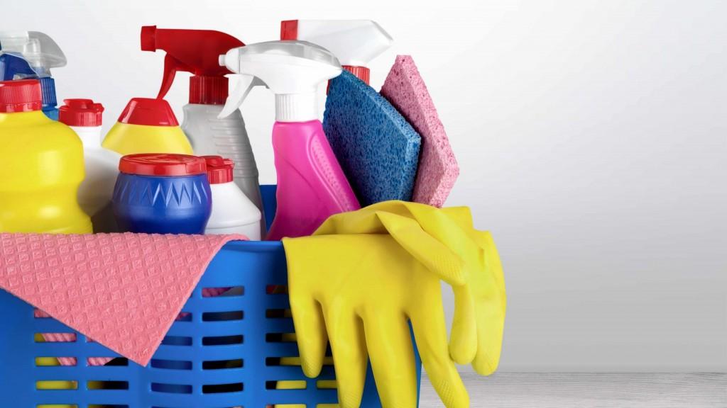 Una canasta con productos de limpieza, atomizadores y productos químicos