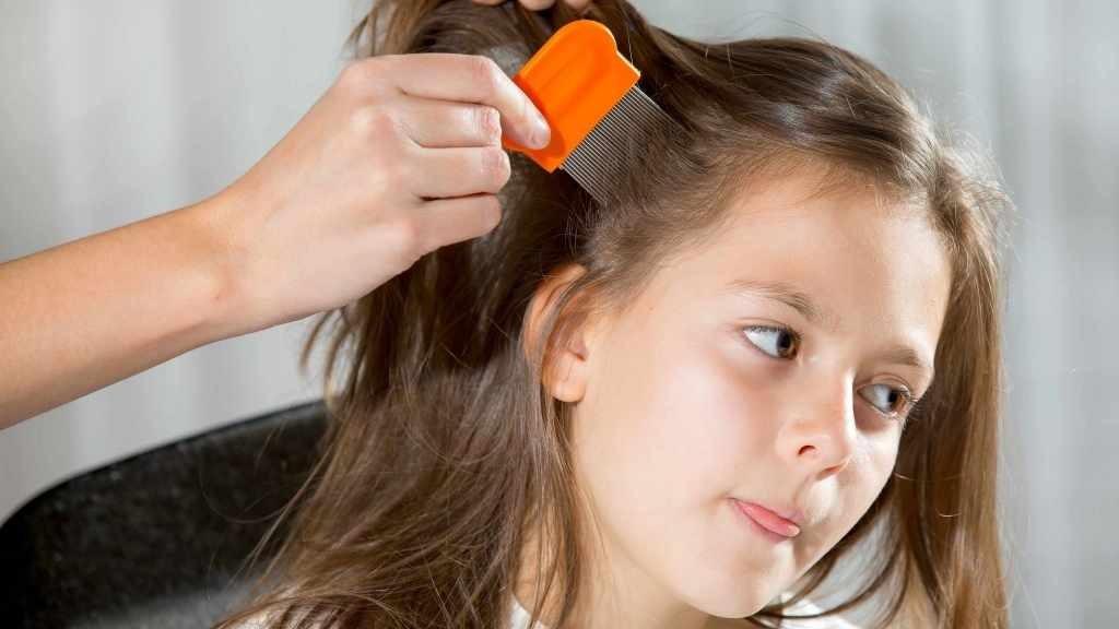 A una niña pequeña se le revisa si tiene piojos