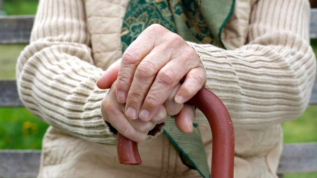 older person sitting with a cane