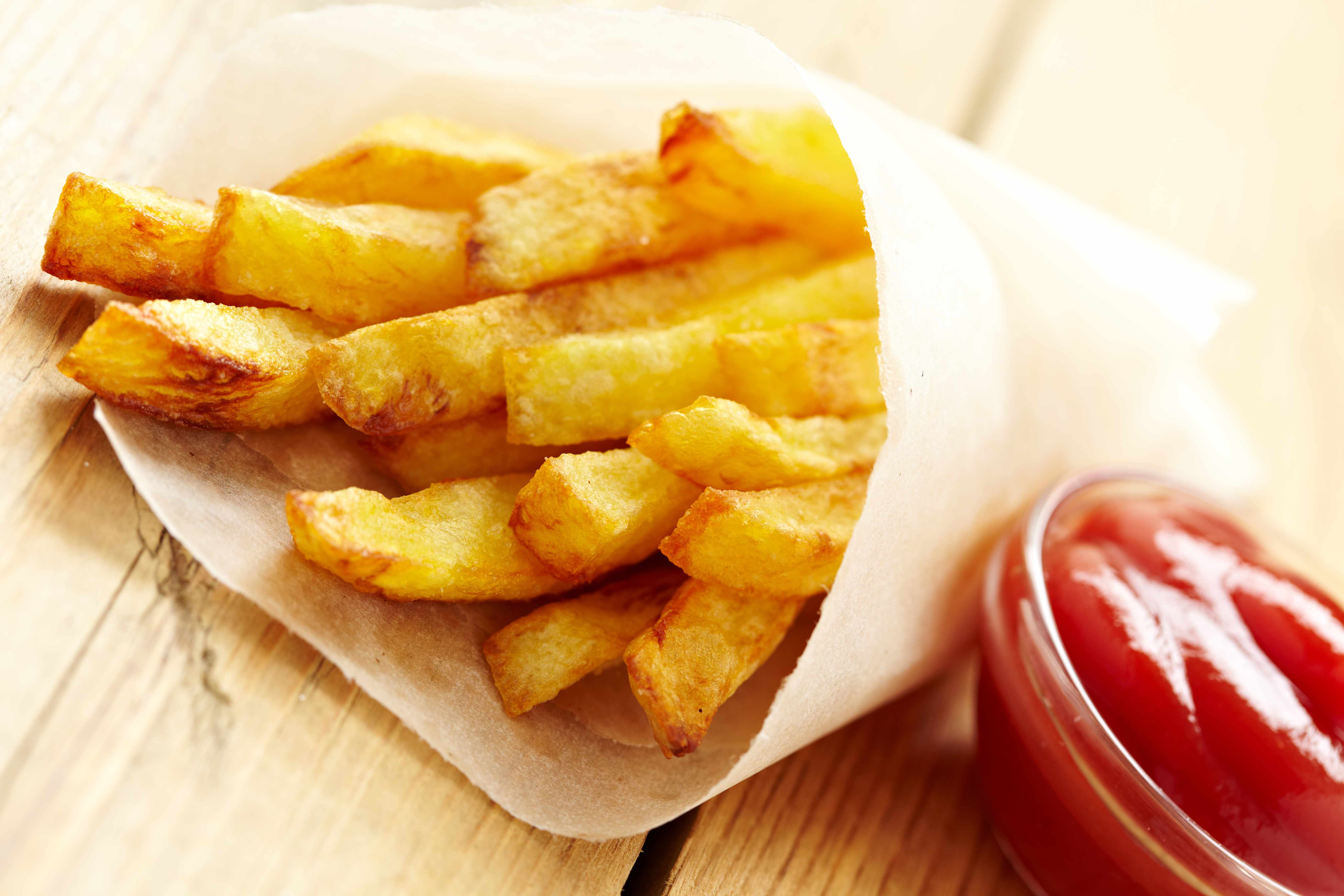 a bag of crispy French Fries and a container of ketchup