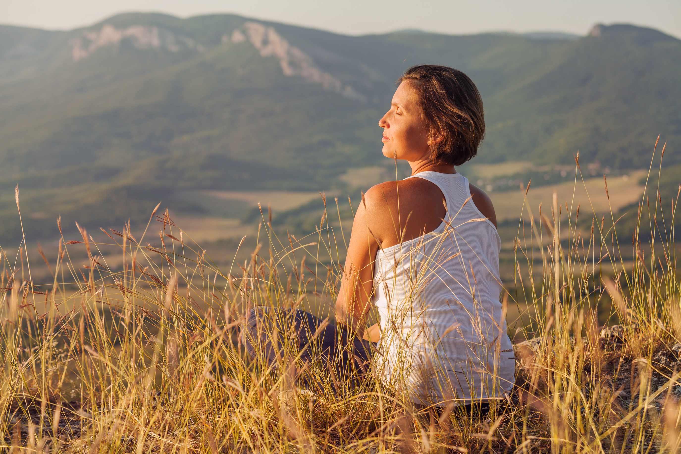 a woman sitting outside in a field enjoying the sunrise
