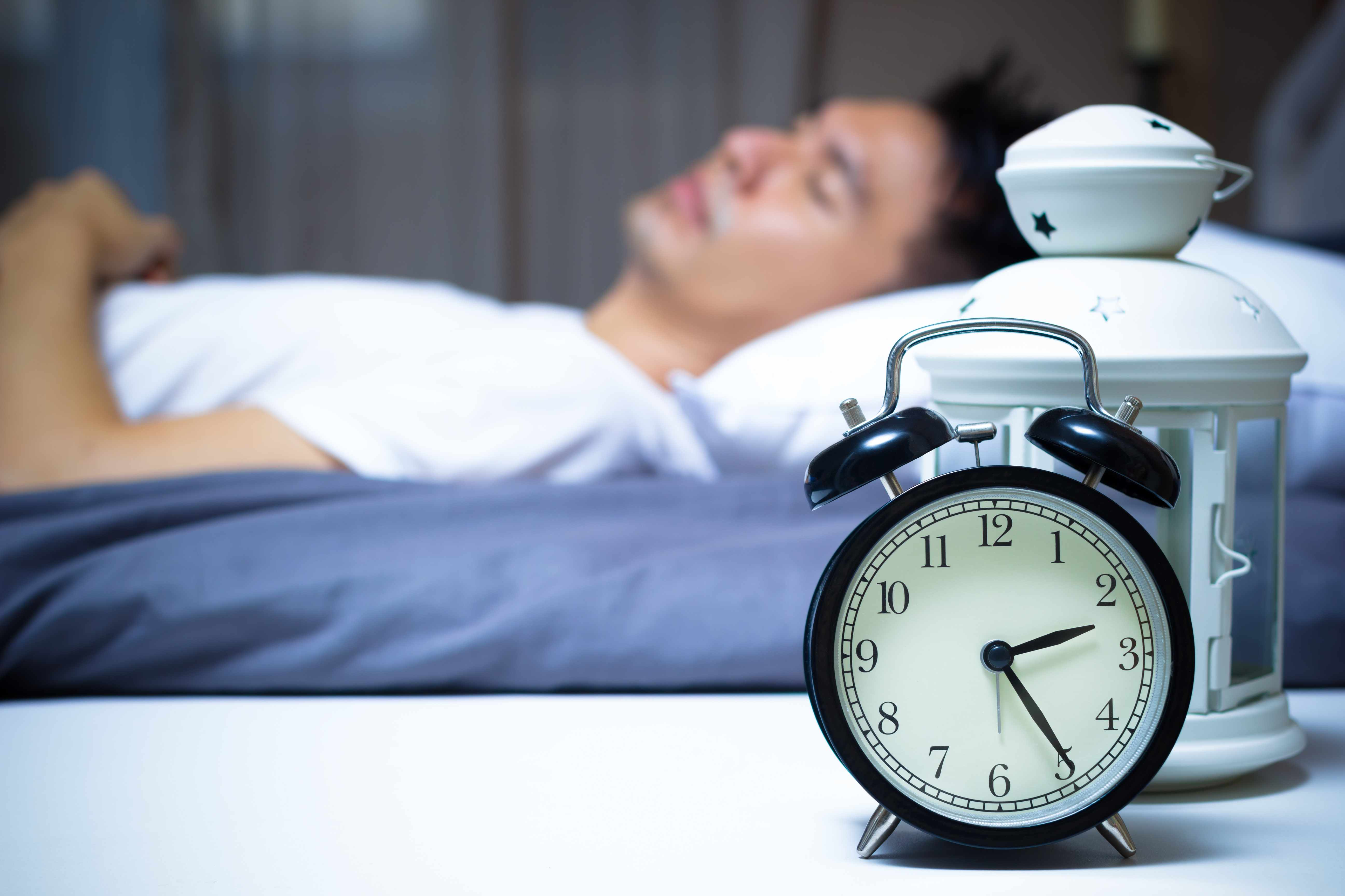 a man sleeping in bed with alarm clock and light on side table