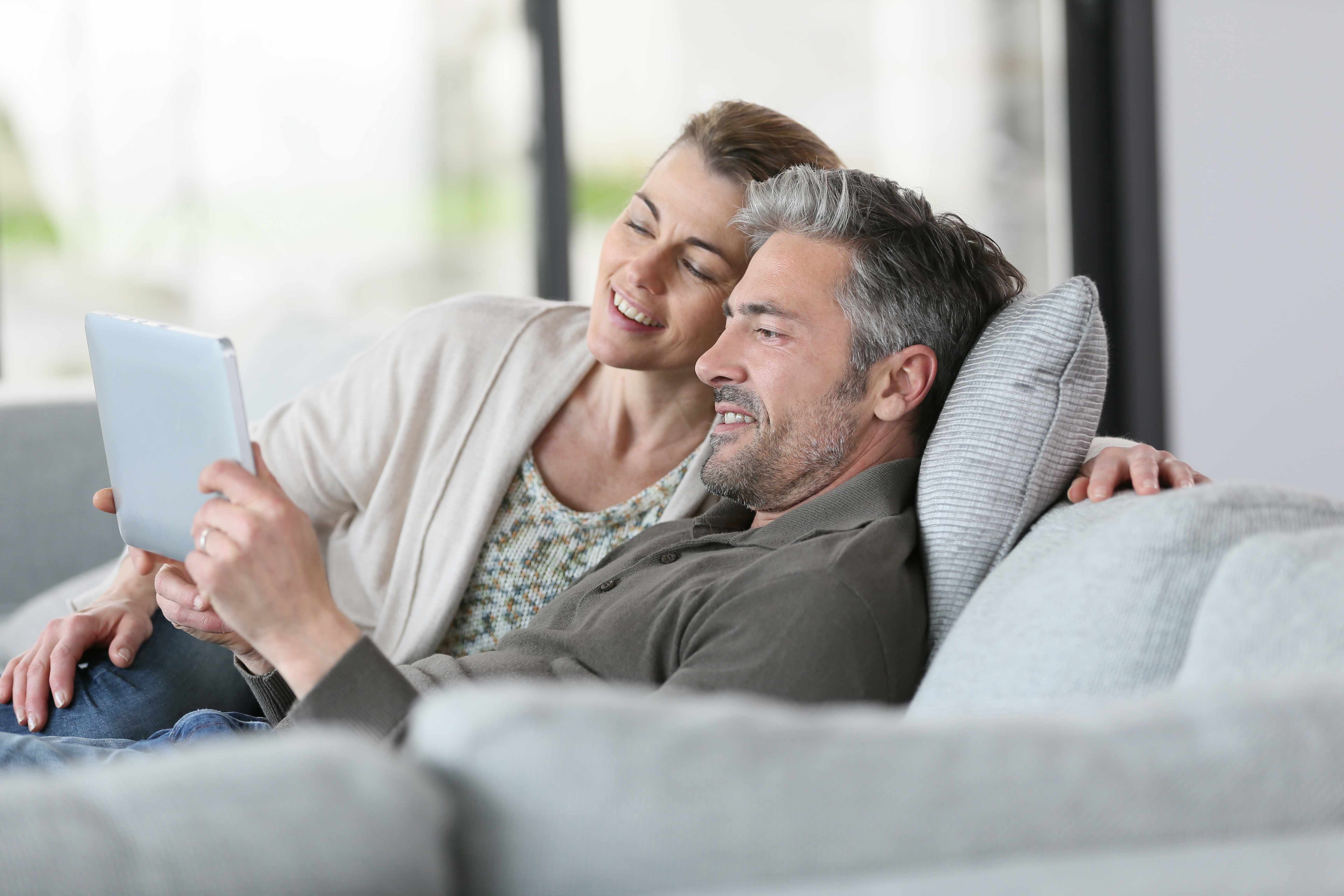 a middle-aged couple with gray hair sitting on a couch looking at a computer tablet