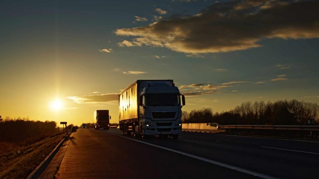 trucks on asphalt highway in a rural landscape at sunset