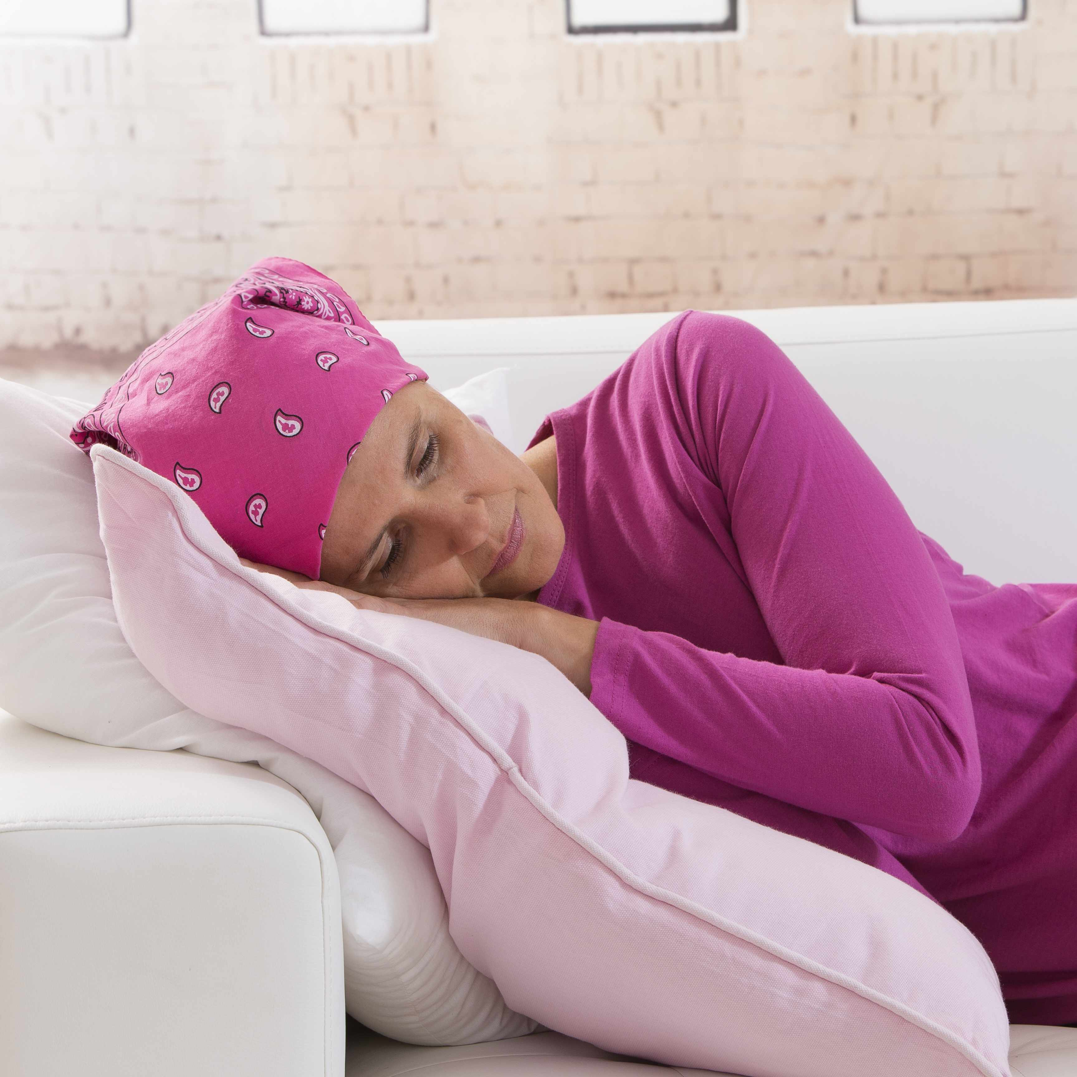 a woman lying on a couch, with a scarf over her head, looking tired, sad