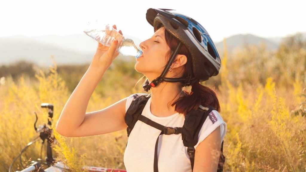 Una mujer anda en bicicleta y bebe agua de una botella
