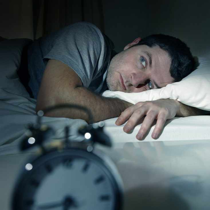 a man in bed in a dark room, with his eyes wide open, looking frustrated, possibly suffering from insomnia or a sleep disorder, with an alarm clock in the foreground