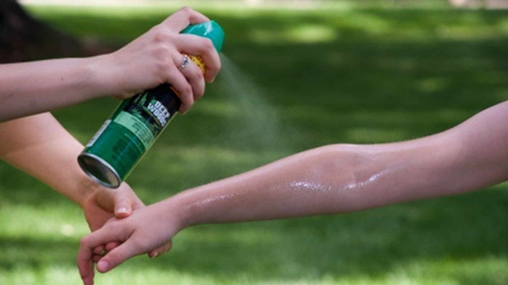 person spraying another person's arm with insect repellent