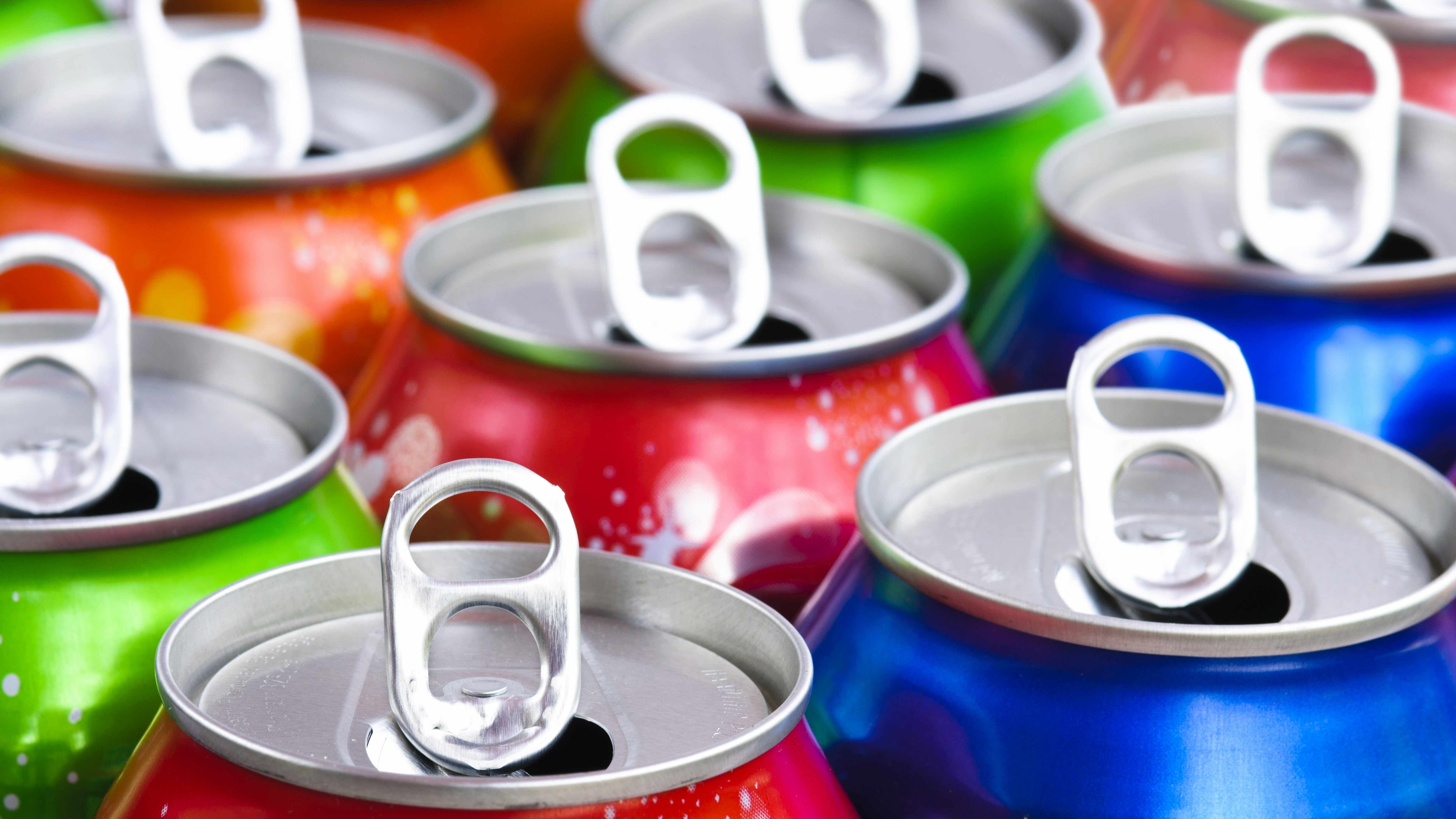 a collection of opened soda cans