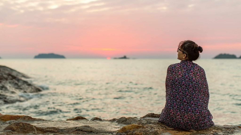a lonely woman wrapped in a blanket sitting on the shore looking at the sunset