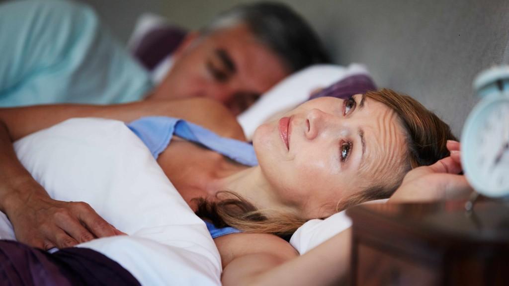 Un pareja en la cama: el hombre duerme, pero la mujer está despierta y parece estar preocupada… quizás sufre de insomnio