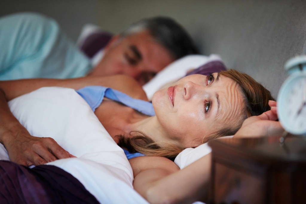 a man and a woman in bed, the man is sleeping, the woman is awake and appears concerned, perhaps suffering from insomnia