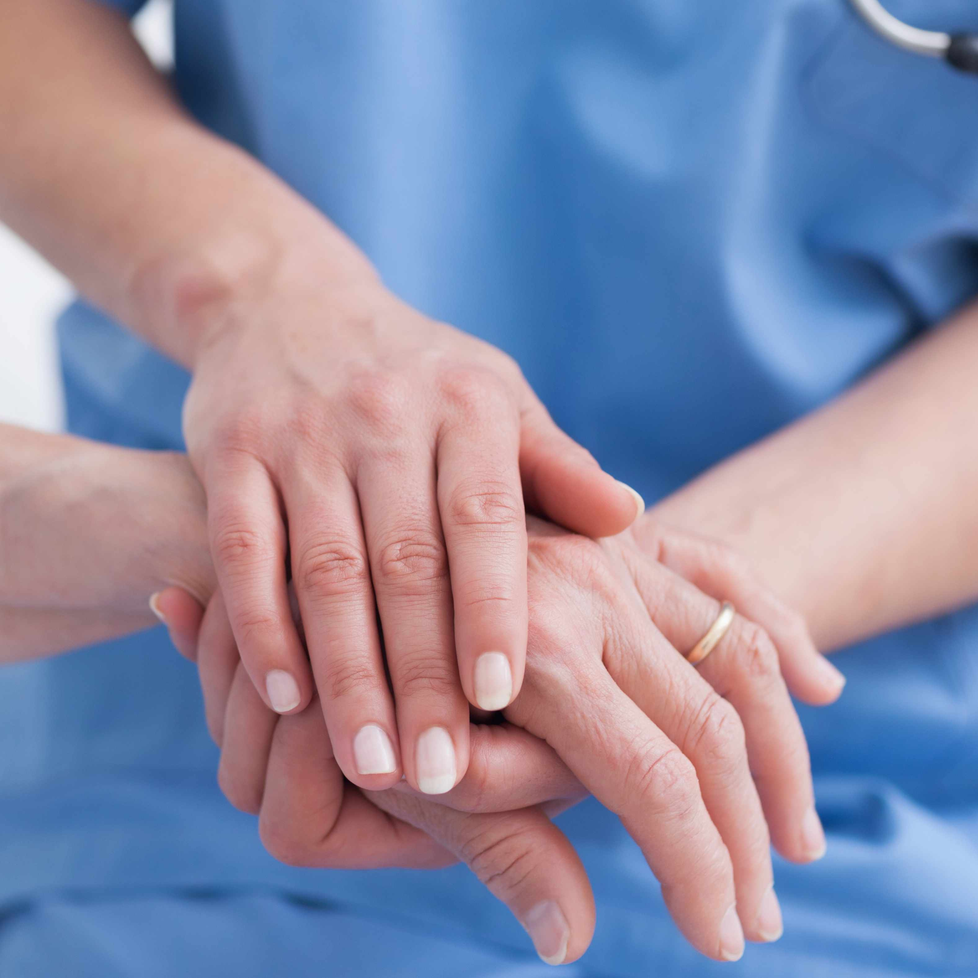 a medical staff person, nurse, holding a patient's hand