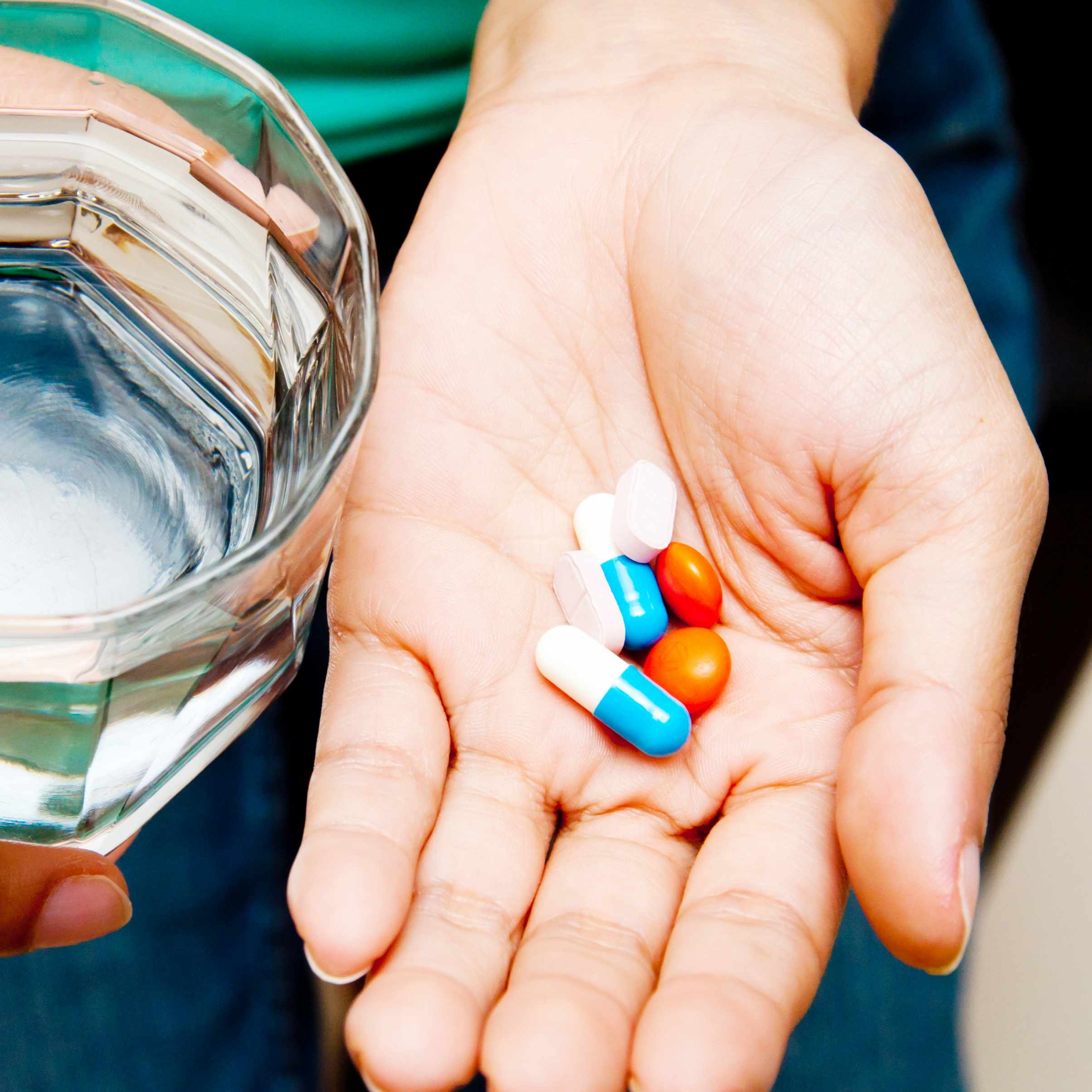 a person holding a glass of water and a handful of medication pills
