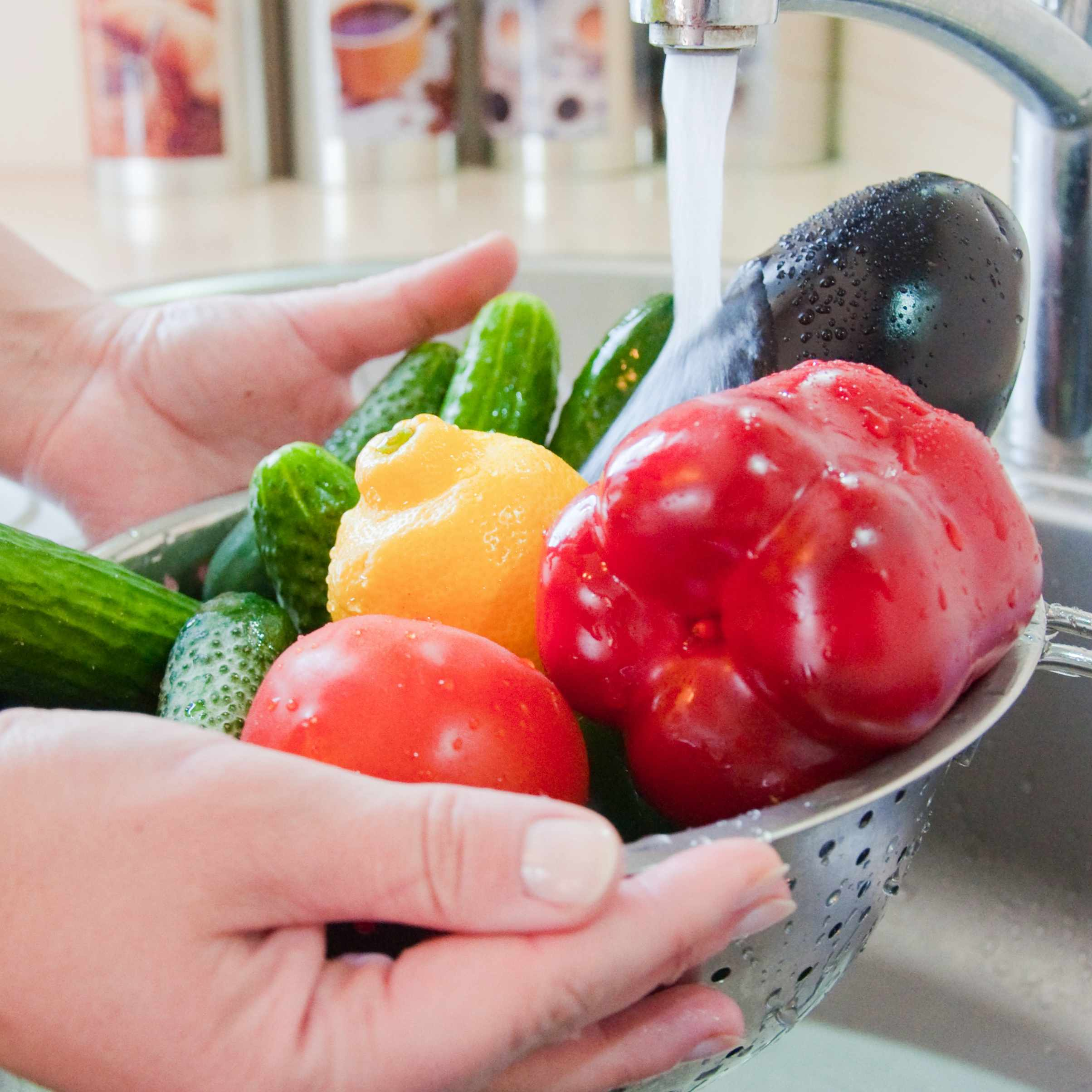 a person washing vegetables and fruits under kitchen water faucet