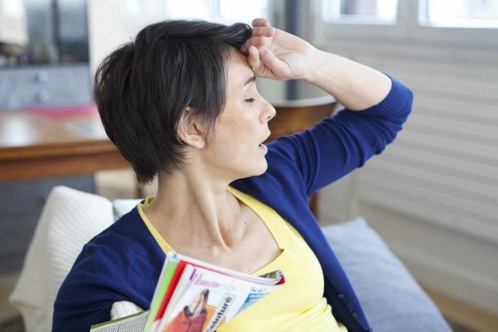 a woman holding her hand to her forehead, suffering from hot flashes caused by menopause