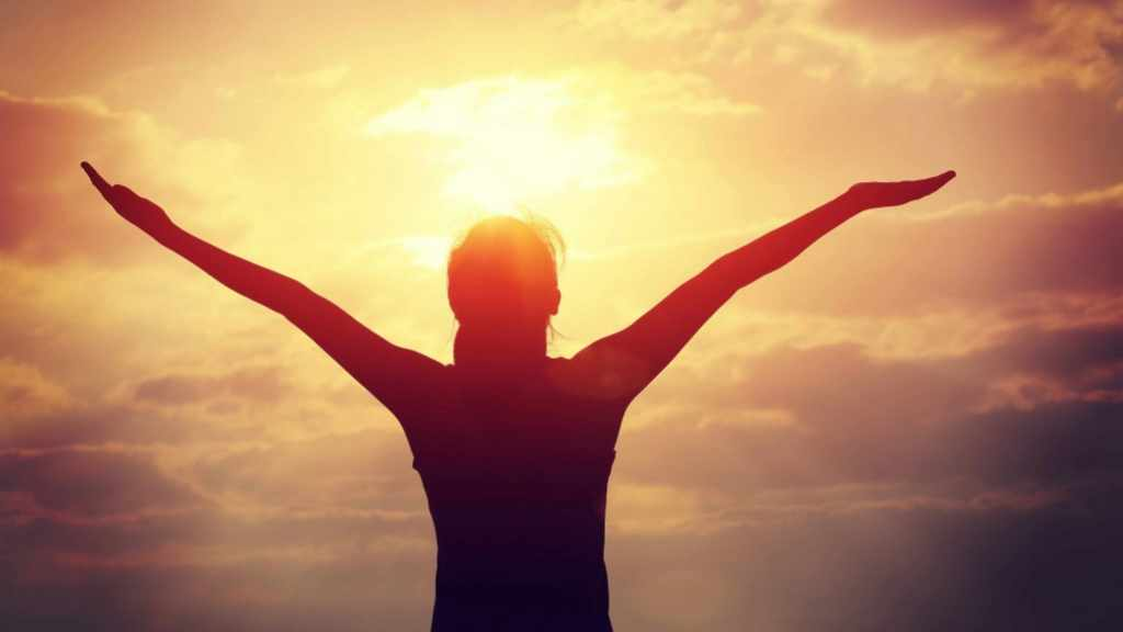 a woman looking at sky and sun with open arms, thankful, grateful