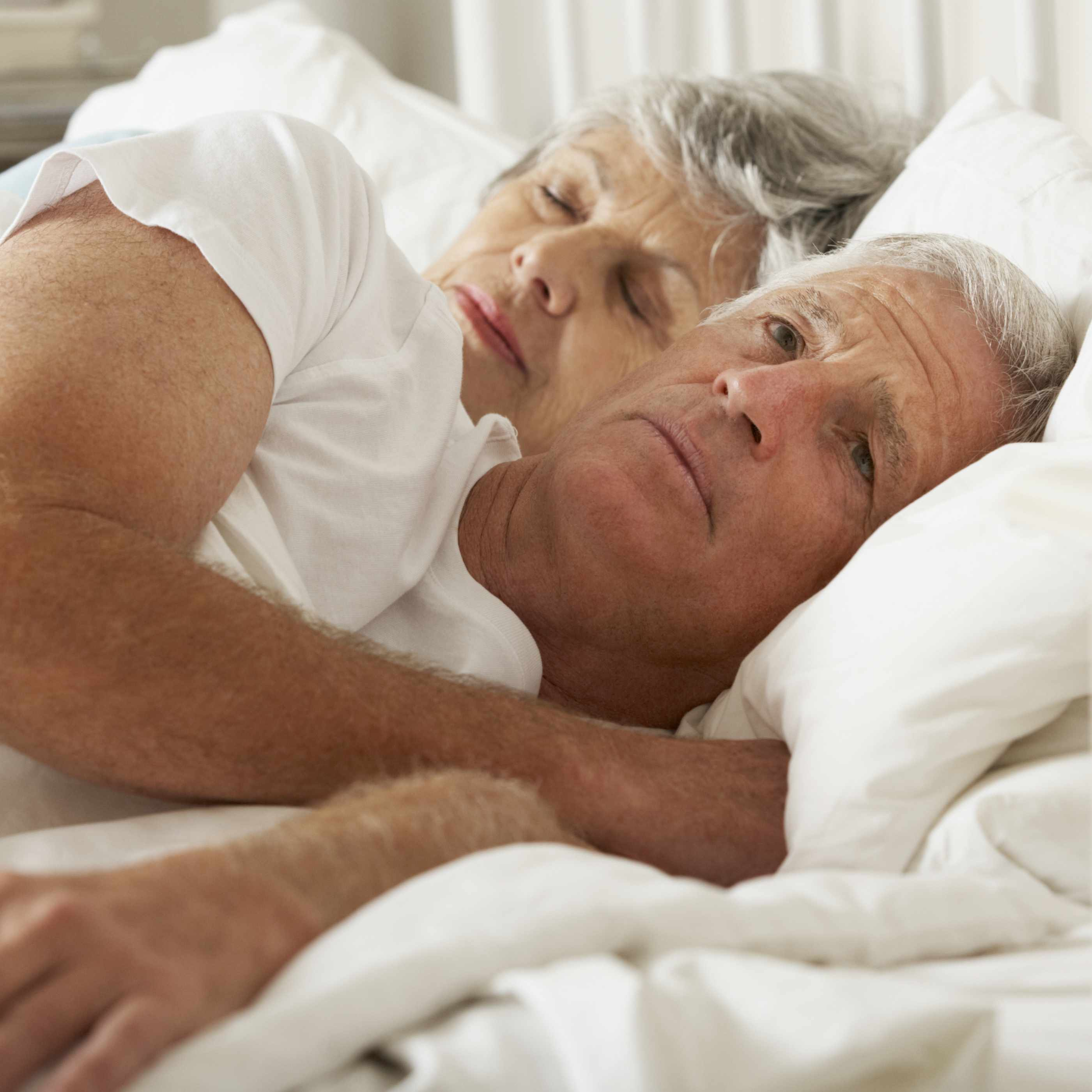 a woman sleeping in bed and a man laying awake