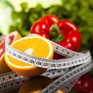 a measuring tape wrapped around food such as fruit and vegetables representing diet