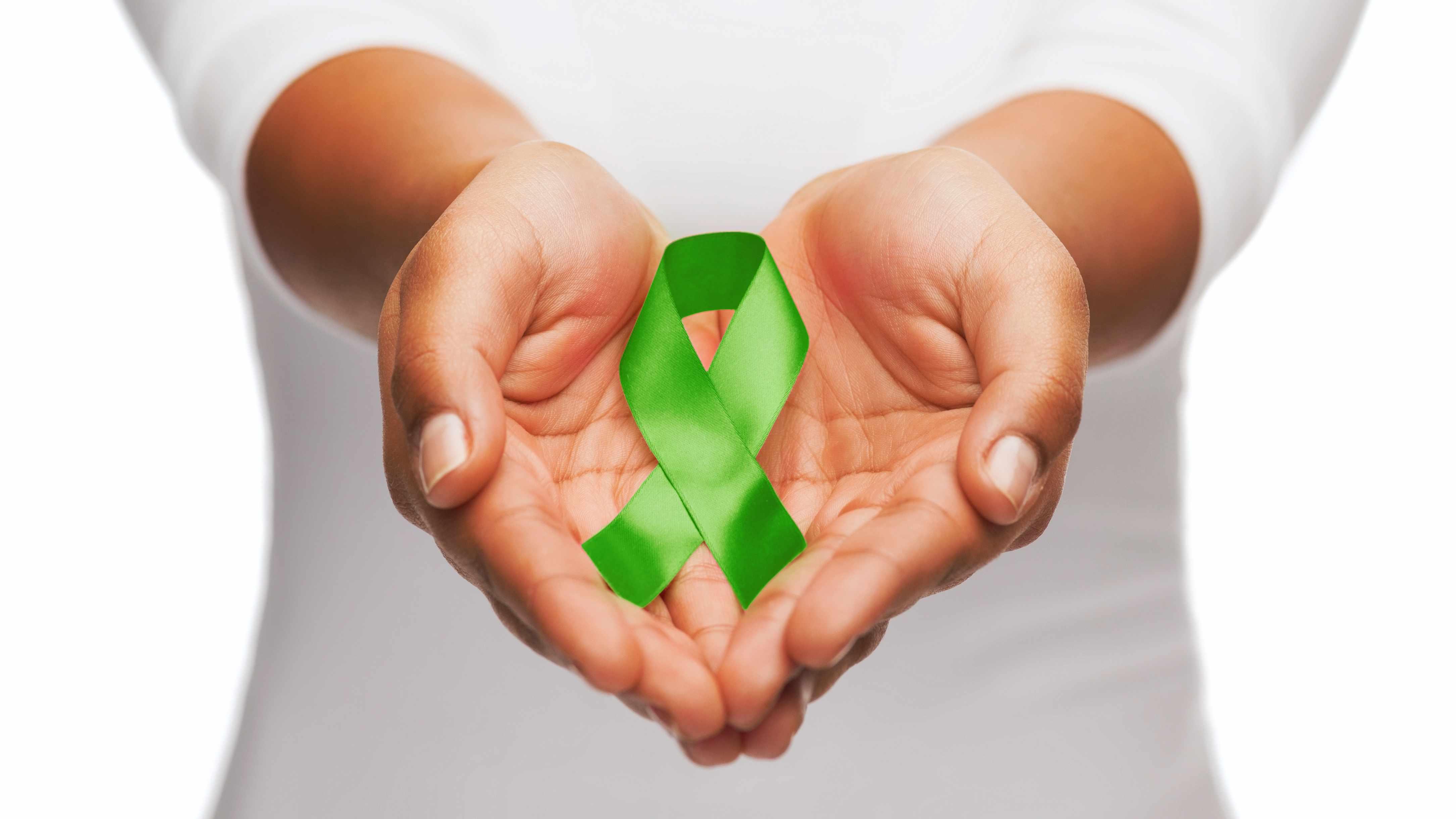 Unas manos femeninas sostienen un cinta verde para concienciación sobre el trasplante de órganos