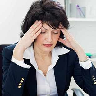 middle aged business woman at desk with headache, migraines, illness, stress, menopause