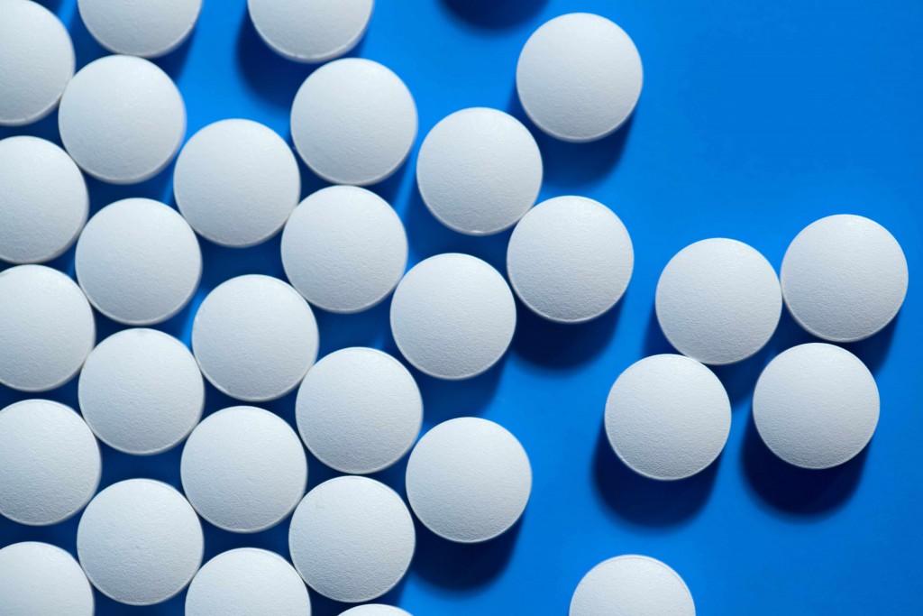 white medicine pills representing aspirin on blue background