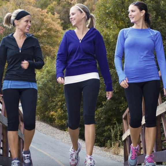 three women walking and exercising together
