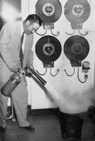 Ken Wiles, night watchman in 1951, demonstrating dousing a fire in a wastebasket
