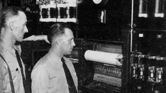 """Mack Ravenhorst and Juel Berg, night watchmen in 1951, checking the chart recorder, which records the """"punching"""" of clocks located on the various floors"""