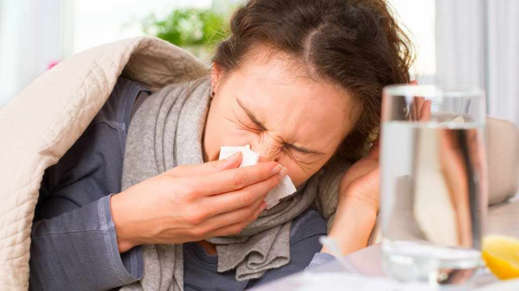 A sick woman in bed sneezing with cold flu allergies