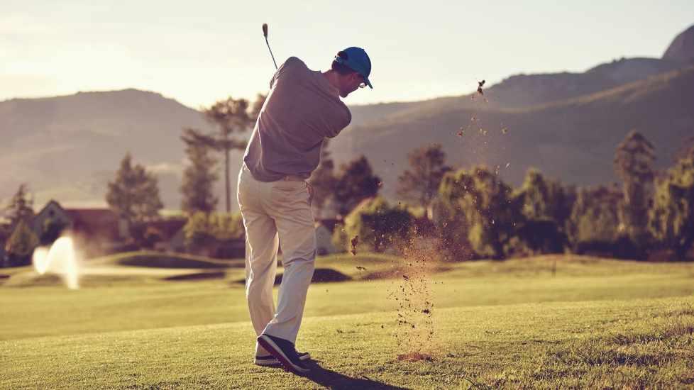 Un golfista da un swing completo