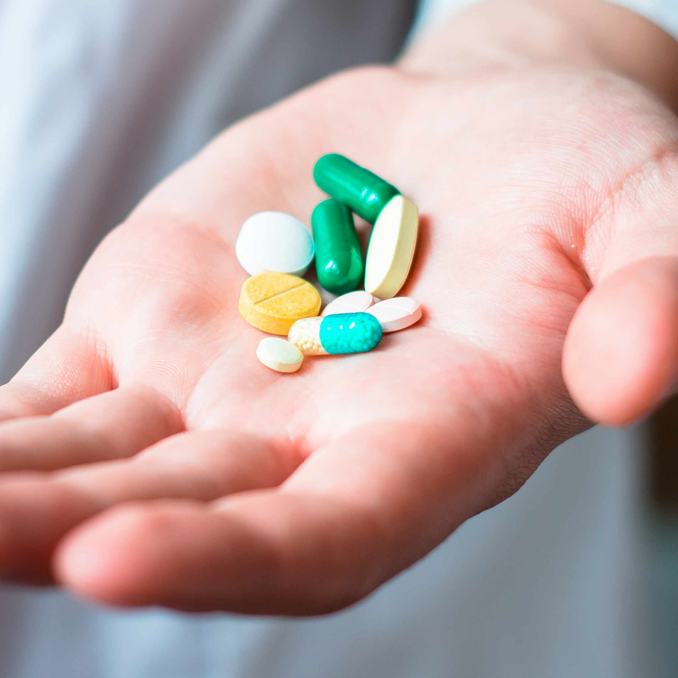 a person's hand full of medicine pills, prescription tablets, vitamins