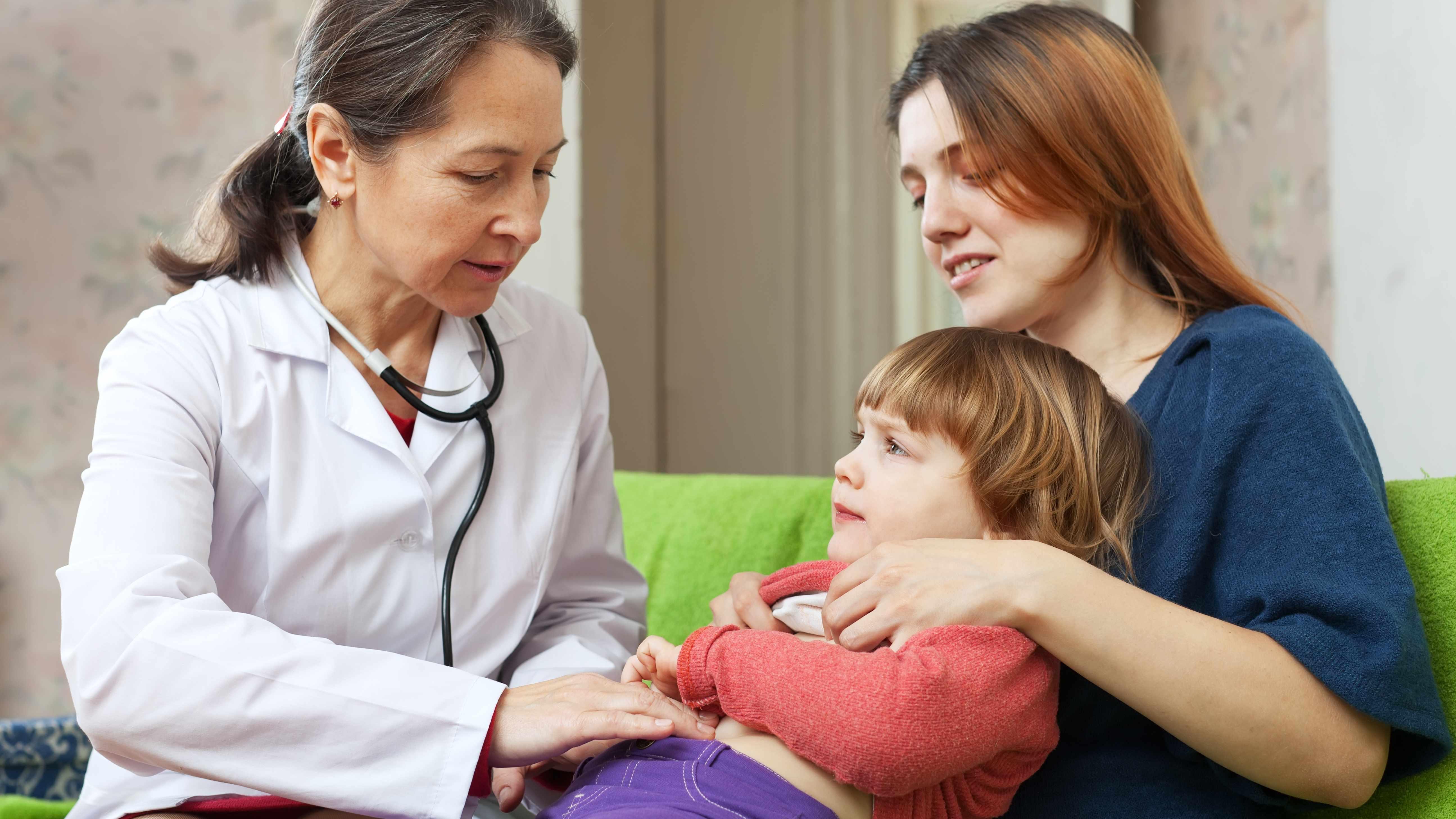 Une médica examina a un niño pequeño que está sentado en el regazo de su madre y le presiona el abdomen.
