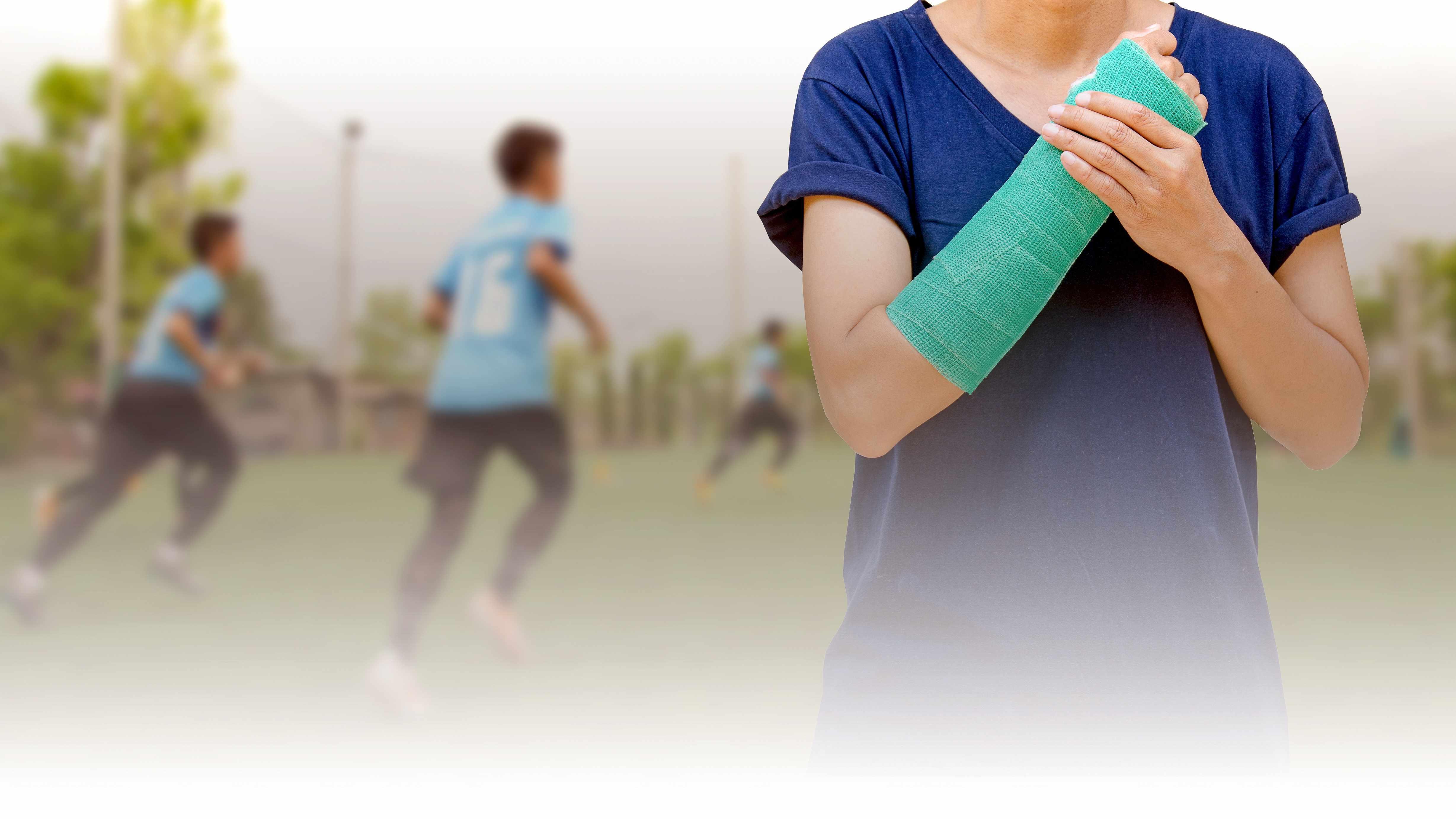 Un adolescente con un yeso en el brazo, que va de la muñeca al codo, de pie frente a otros adolescentes que juegan fútbol