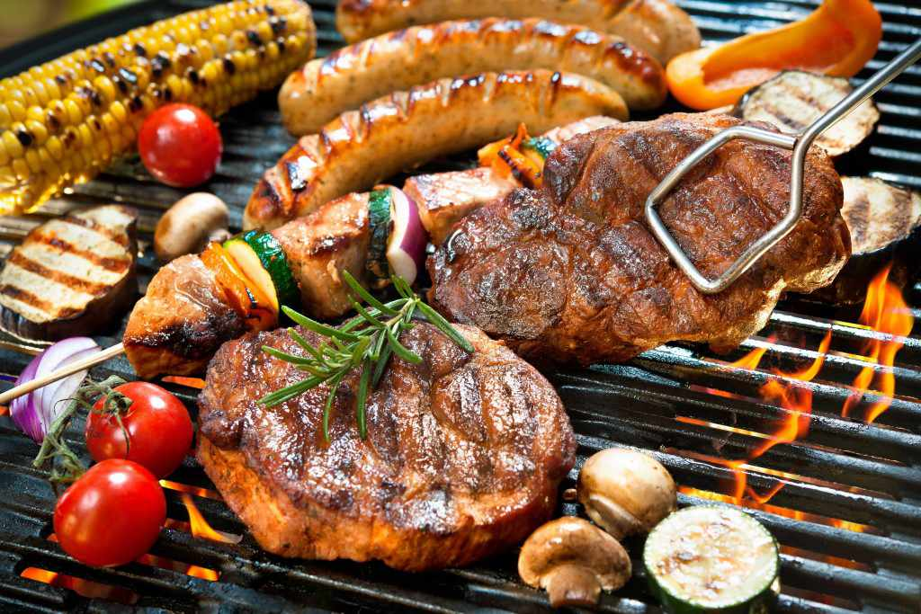 steak, meat, brats and vegetables cooking over a barbecue grill