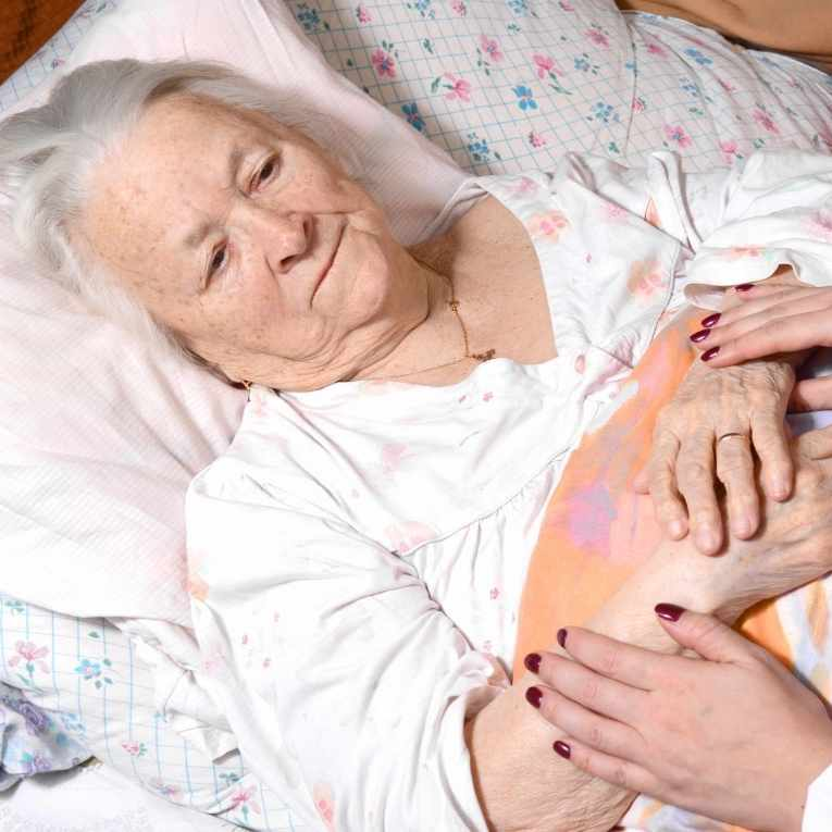elderly woman in bed, caretaker holding her hands